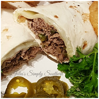 Philly cheesesteak wrap on a plate with onion rings