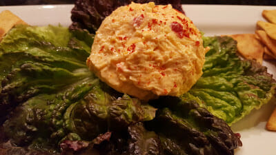 Pimento Cheese on a bed of lettuce on a white serving platter