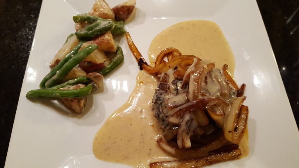 hamburger steak with caramelized onions and green beans on a white plate
