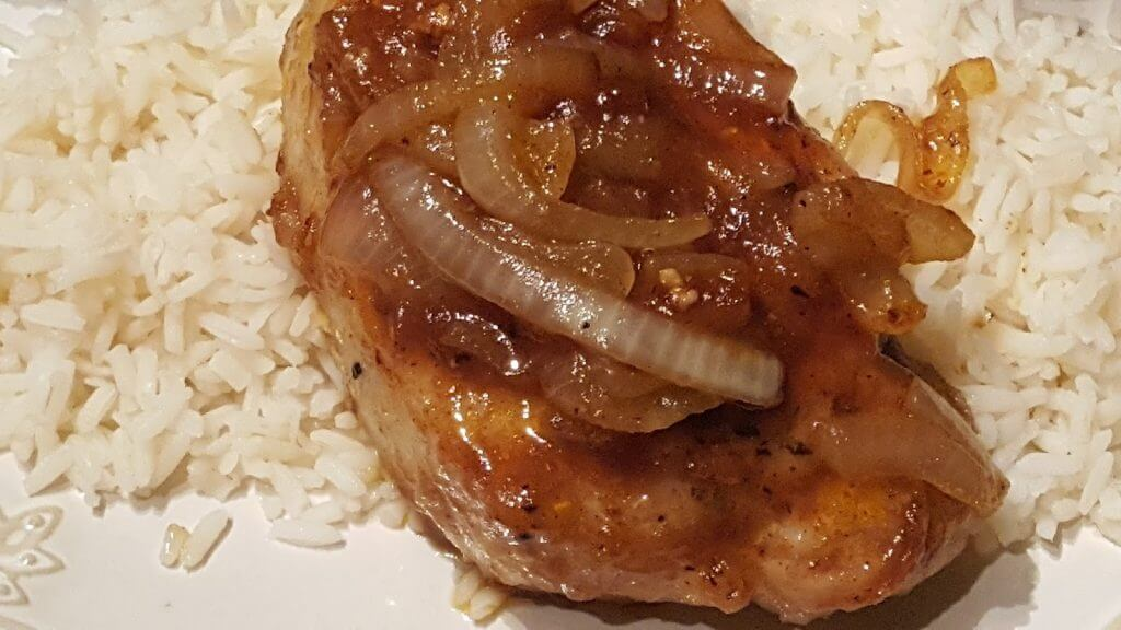cooked glazed pork chop on a bed of rice