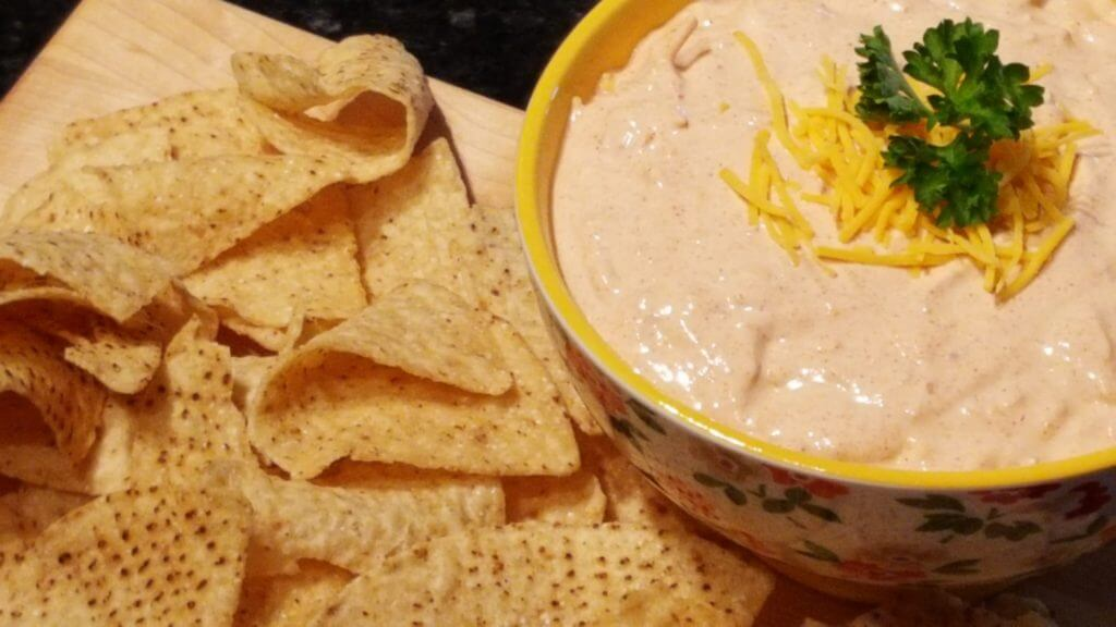 Easy Taco Dip Recipe in a bowl with tortilla chips on the side