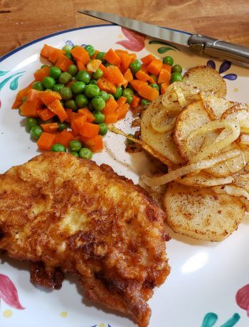 Southern Pan Fried Pork Chops on a plate with fried potatoes, peas and carrots from Julia's Simply Southern