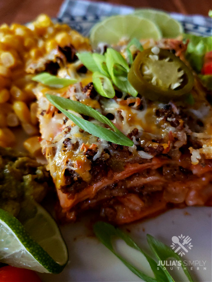 Delicious Enchilada Casserole Recipe garnished with scallions and a sliced pickled jalapeno
