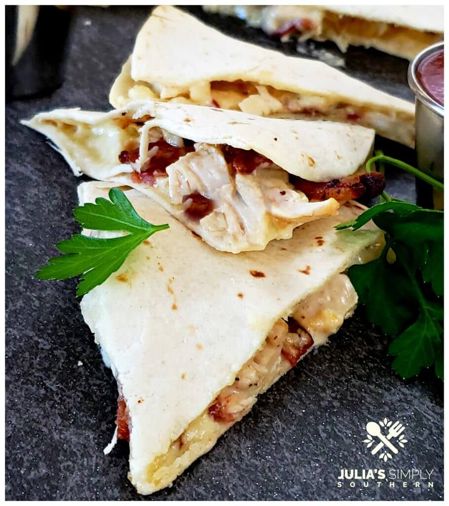 Oven baked quesadillas with chunks of chicken, bacon, melted cheese and ranch on a flour tortilla