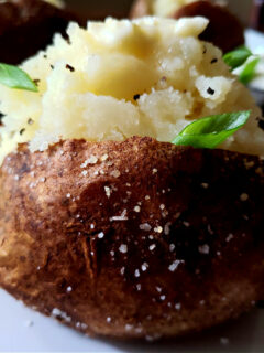 Fluffy Baked Russet Potatoes served on a white plate garnished with scallions