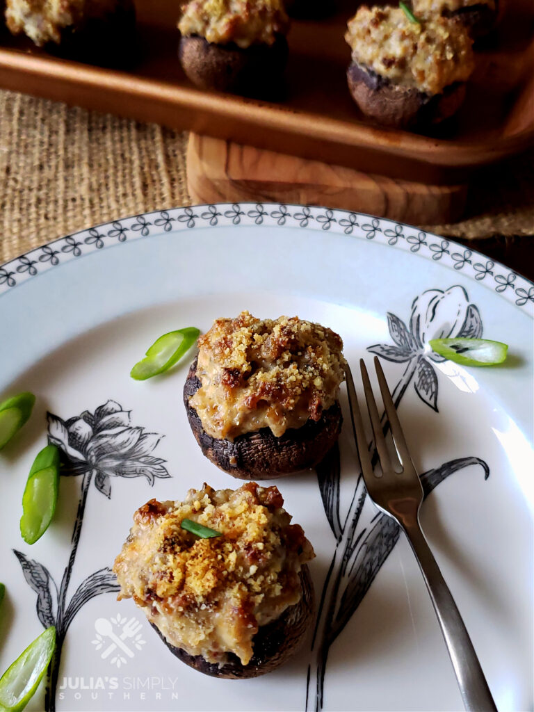 Awesome Easy Sausage Stuffed Mushrooms hors d'oeuvres on a small appetizer plate garnished with spring onions
