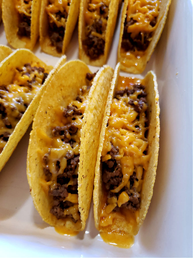 Baked tacos with ground beef and cheddar cheese in hard shells. Easy Cheesy Oven Baked Tacos.