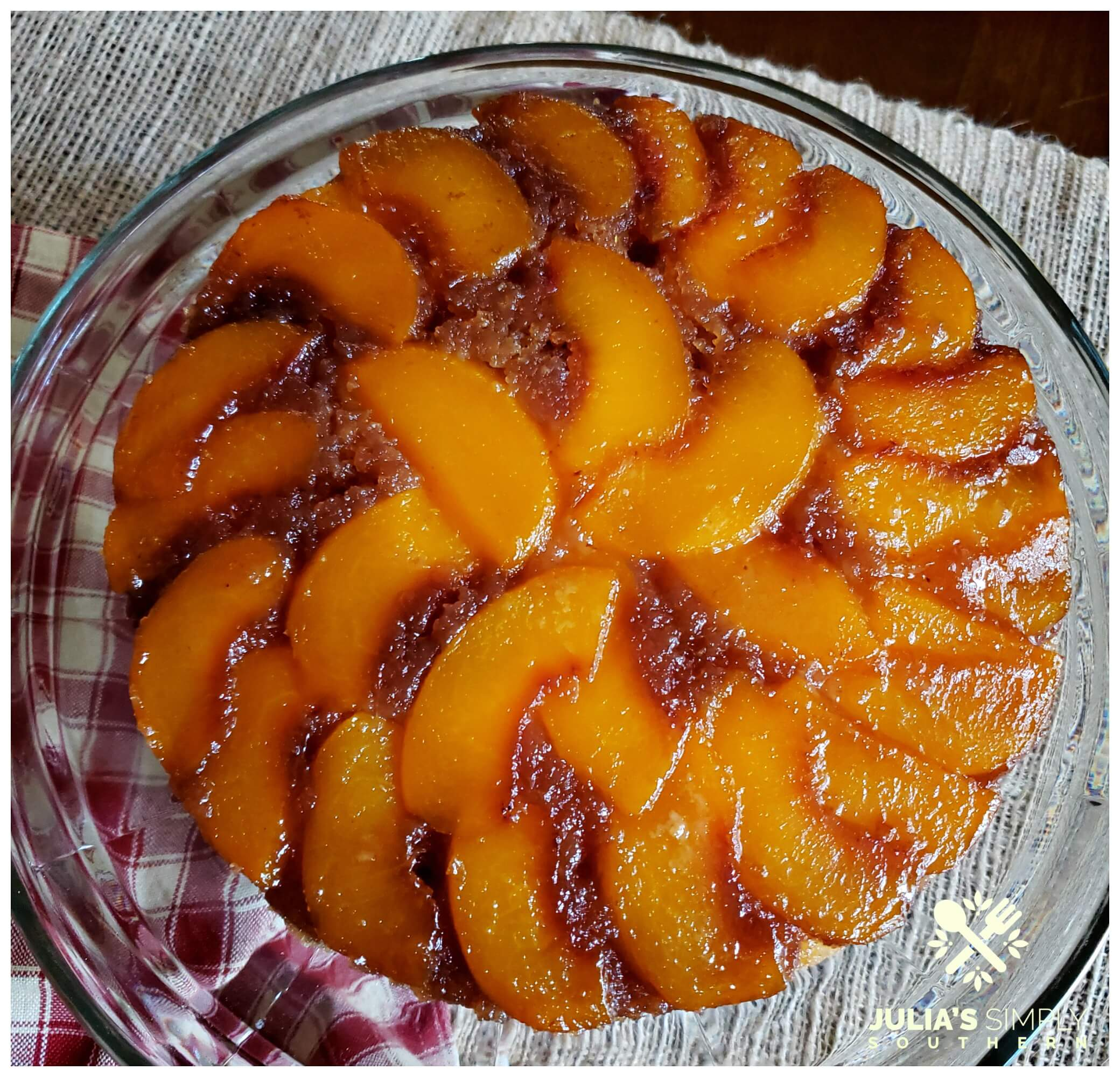 Beautiful caramel peach upside down cake with freestone Pretty Lady Peaches on a glass plate and country check napkin