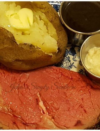 Perfect Prime Rib served on a plate with a baked potato, au ju and horseradish cream