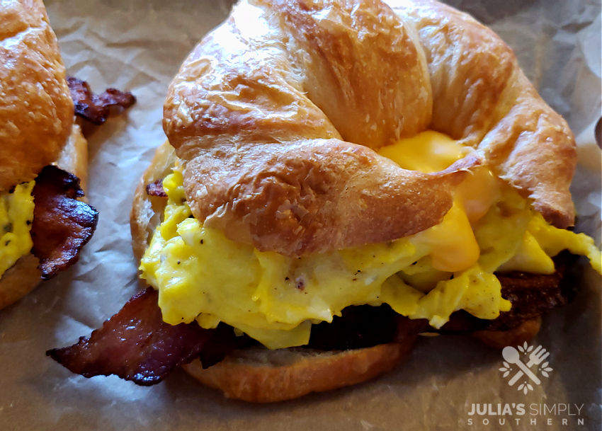 bacon egg and cheese croissant sandwiches on a sheet pan lined with parchment