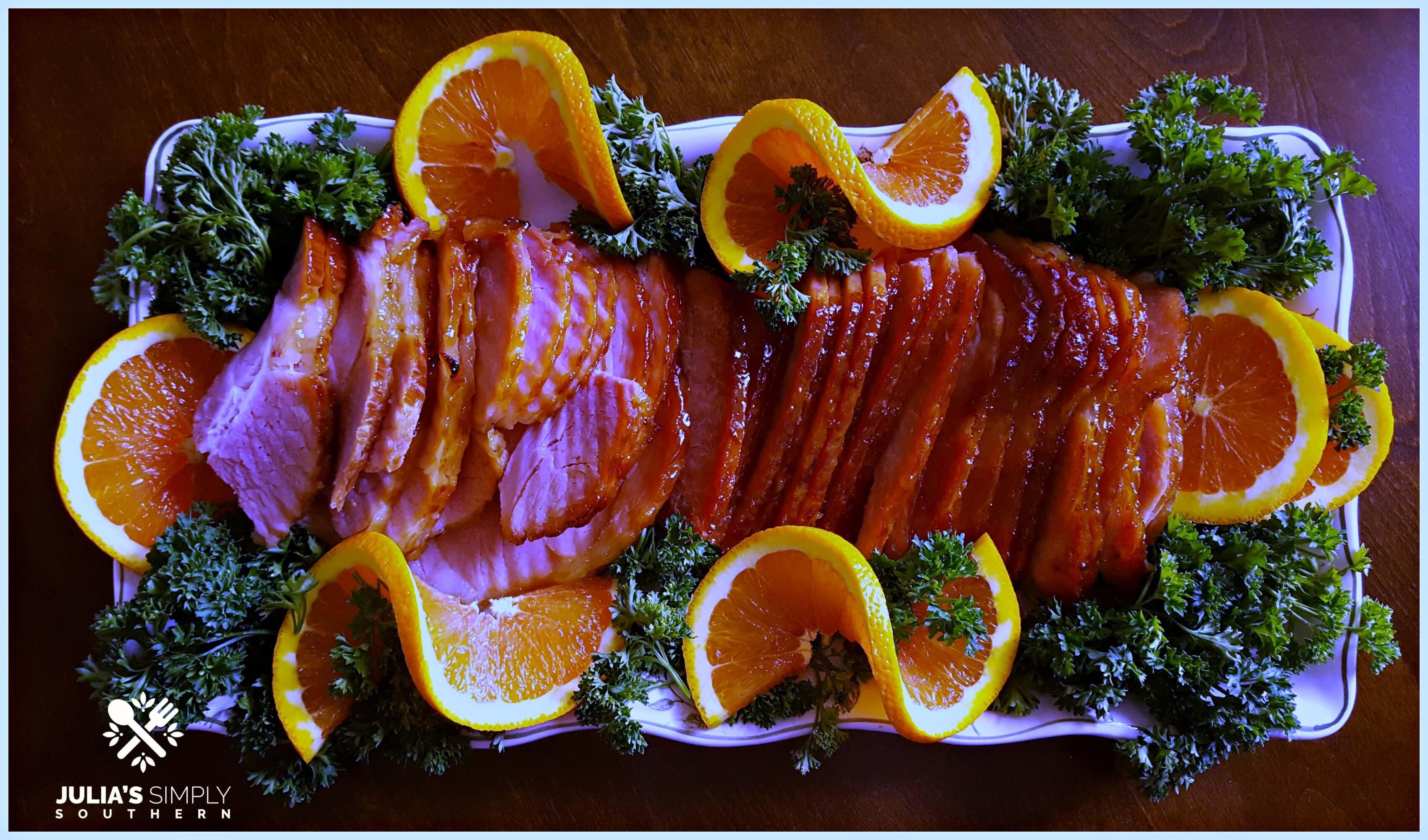 Glazed Ham Recipe for Glazed Ham with a Honey Orange Glaze on a serving platter garnished with orange slices and parsley