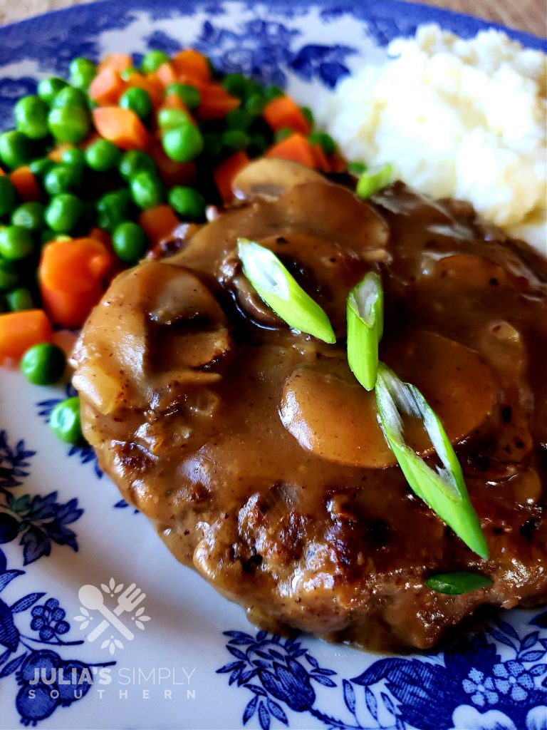 Blue and white plate with Salisbury Steak and mushroom gravy garnished with scallions