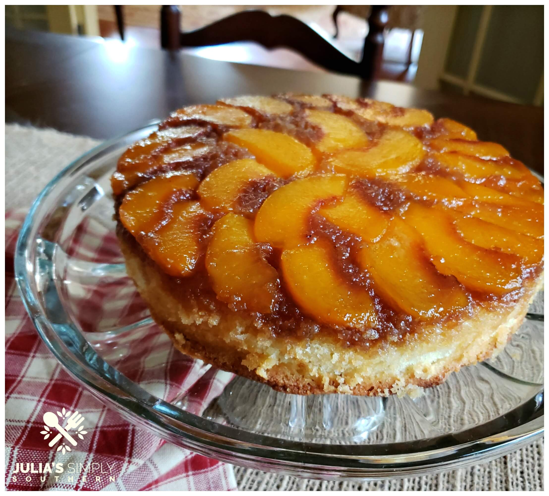 Best peach cake - alton - dessert recipes - Southern upside down peach cake on a glass cake stand in a country style dining room