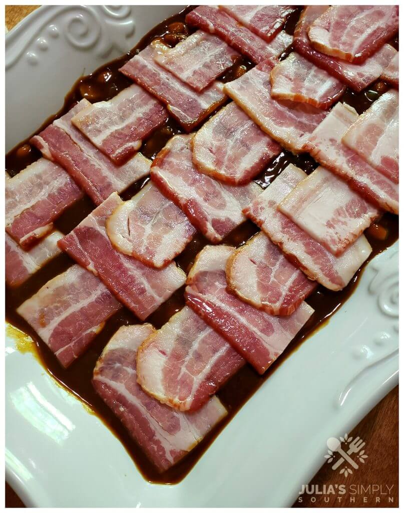 Easy recipe for homemade baked beans topped with thick bacon pieces
