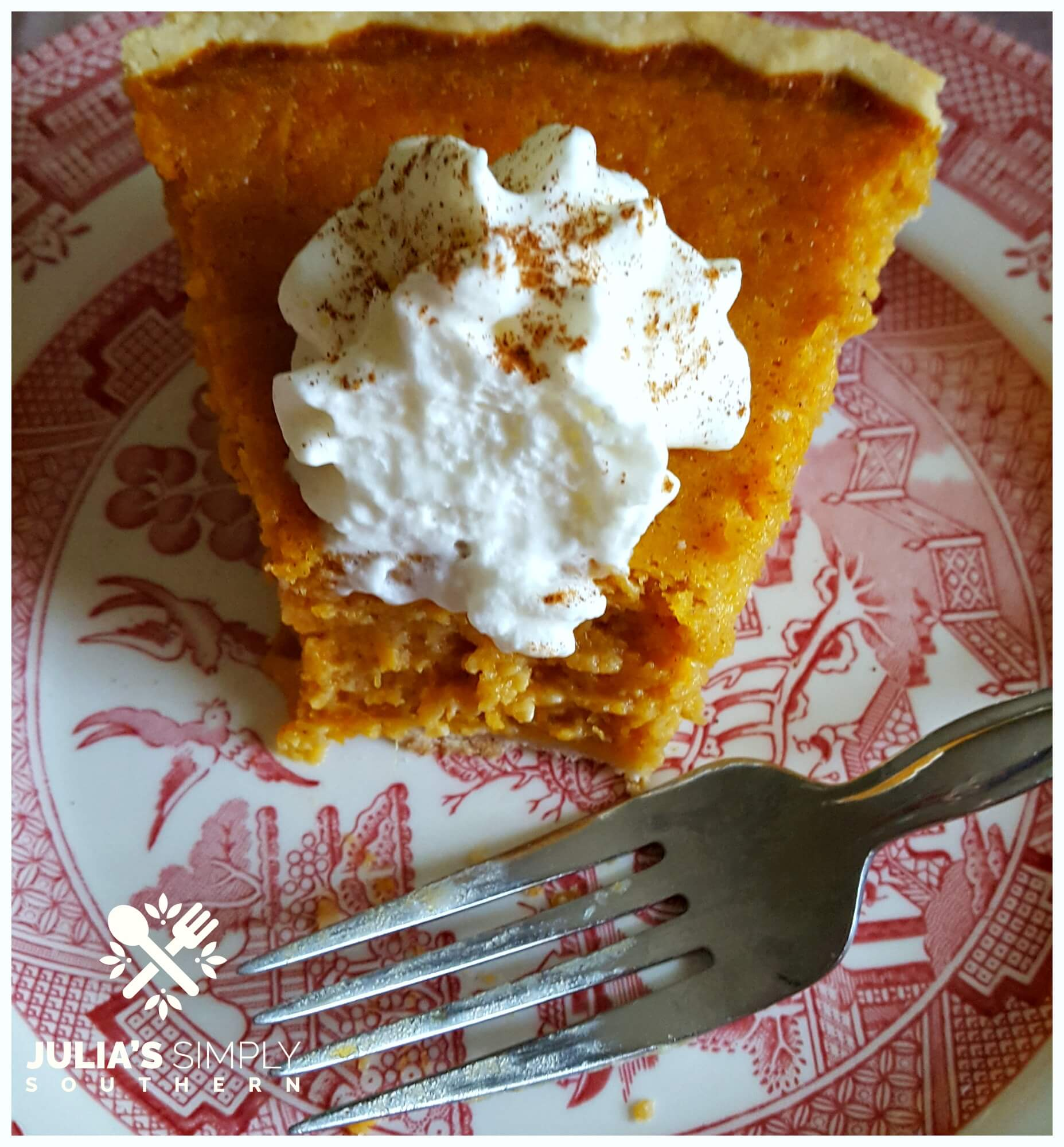 Delicious pie of Southern sweet potato pie topped with whipped cream on a red and white china plate