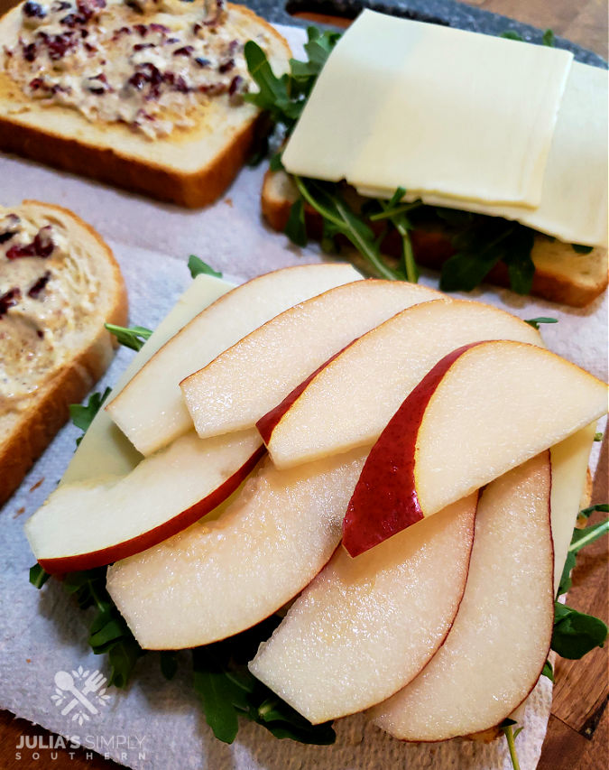 building turkey sandwiches with sliced pear, white cheddar, arugula and a cranberry spread