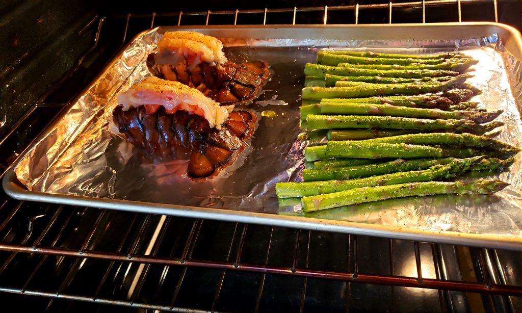 Sheet pan with lobster tails and asparagus for Broiled Lobster Tail Recipe