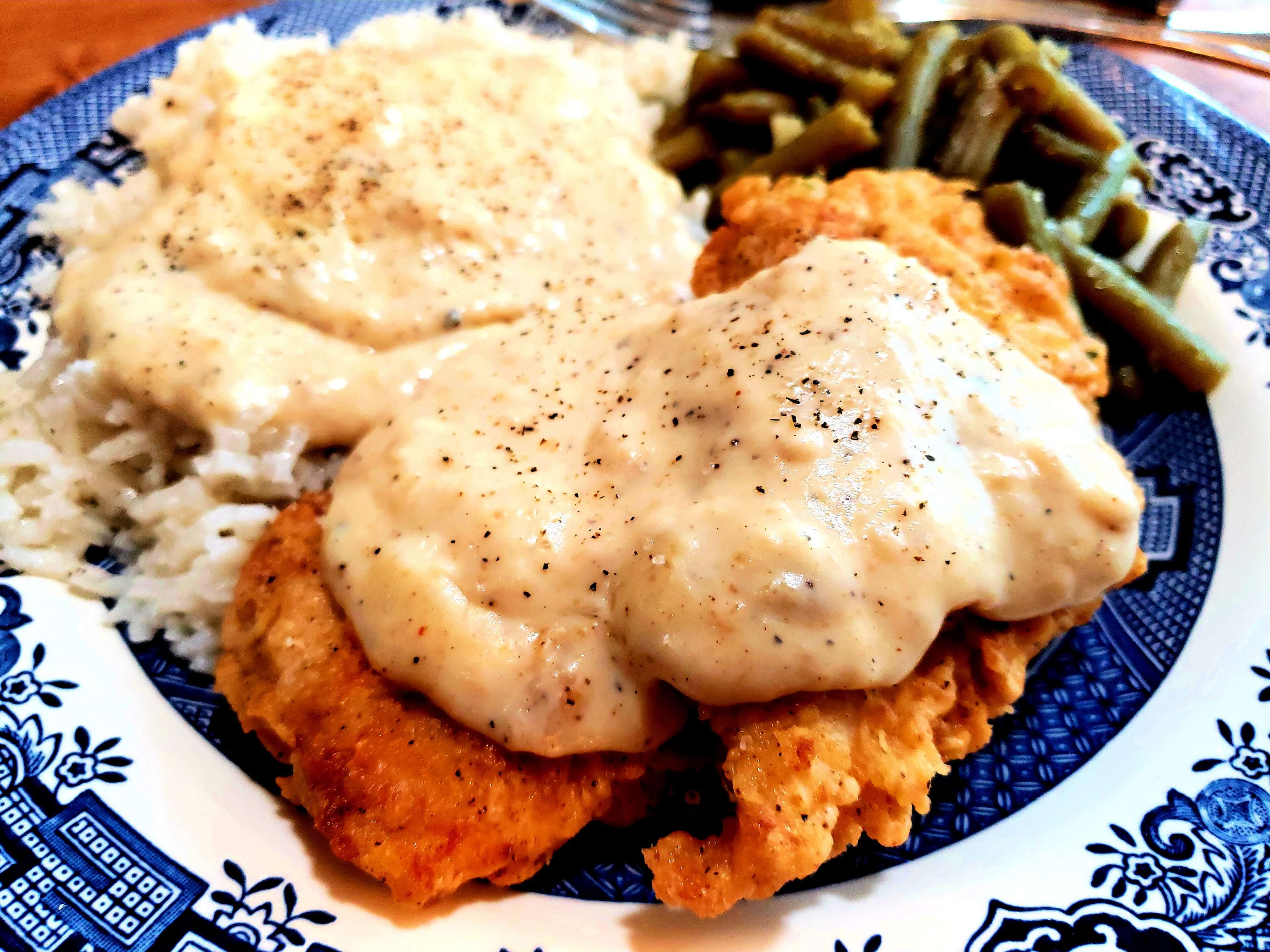 Herb Seasoned Southern Fried Boneless Chicken Breast on a plate with rice and gravy and green beans