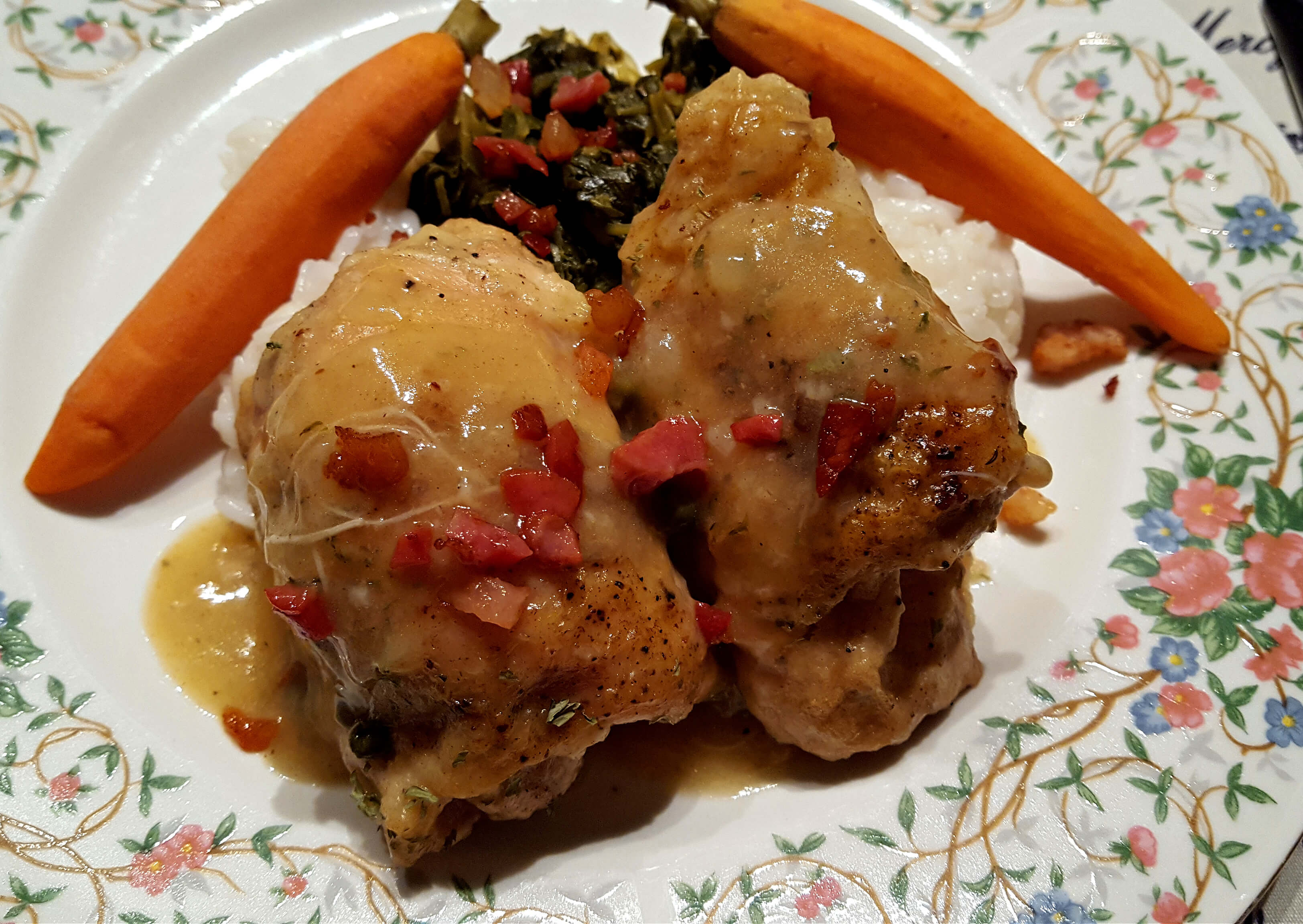 Braised Chicken Thighs on a dinner plate with carrots and greens