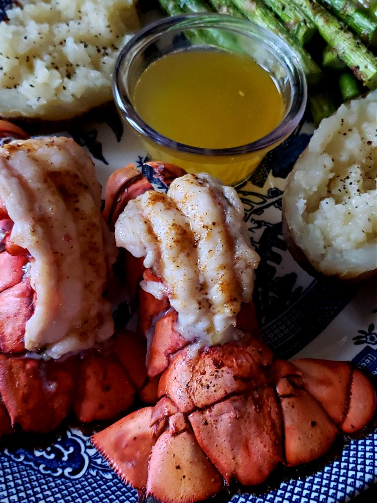 Broiled Lobster Tails on a serving platter with clarified butter, baked potatoes and asparagus
