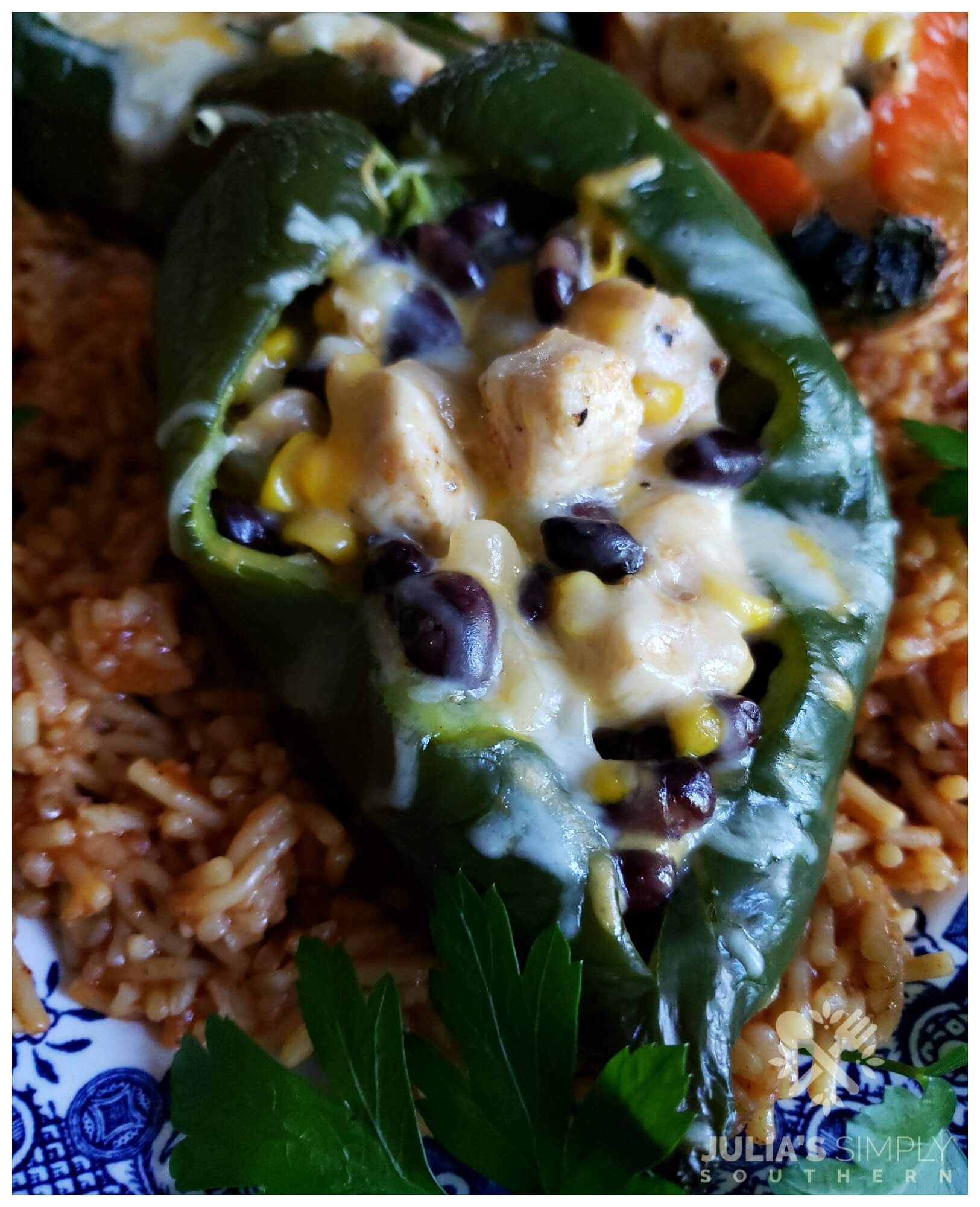 Fresh baked poblano pepper stuffed with chicken, cheese, corn and black beans and served on a bed of Spanish rice. The best stuffed pepper recipe with poblanos.