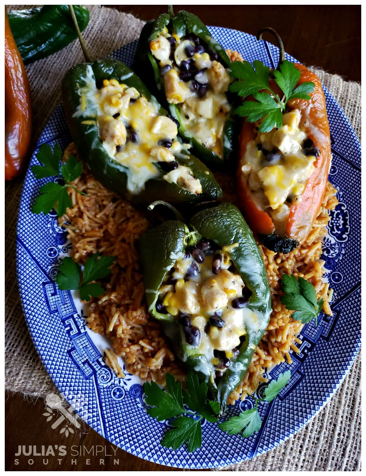 Blue and White Platter with Chicken and cheese stuffed poblano peppers on a bed of red spanish style rice garnished with parsley - Best stuffed peppers southwest style ever