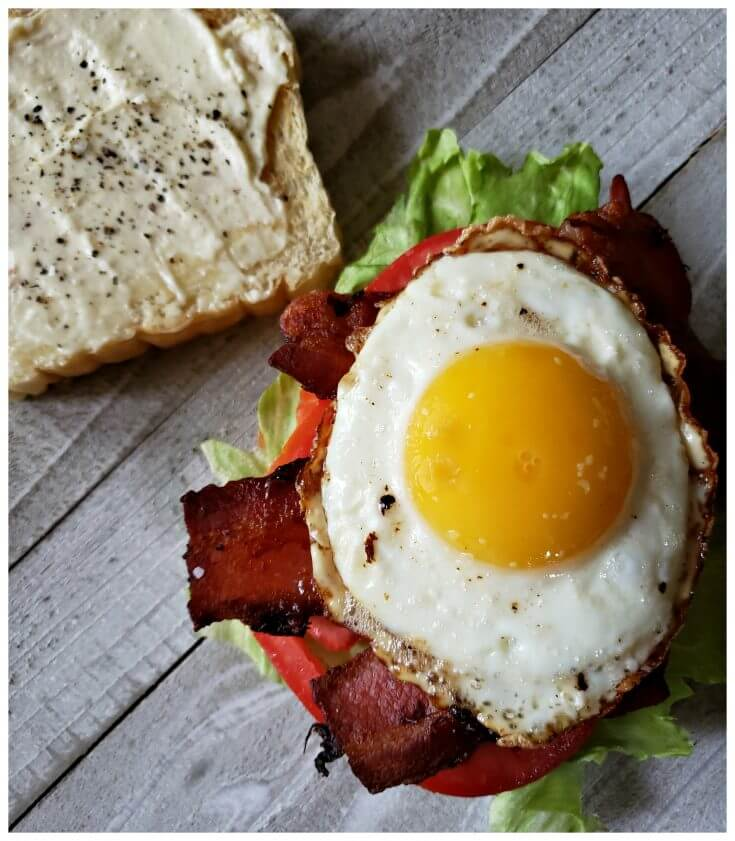 Best BLT Sandwich Recipe with fried egg for breakfast. The perfectly cooked egg with runny yolk sits on top of crispy bacon, crisp lettuce and a fresh vine ripe tomato on toasted bread for the ultimate breakfast.