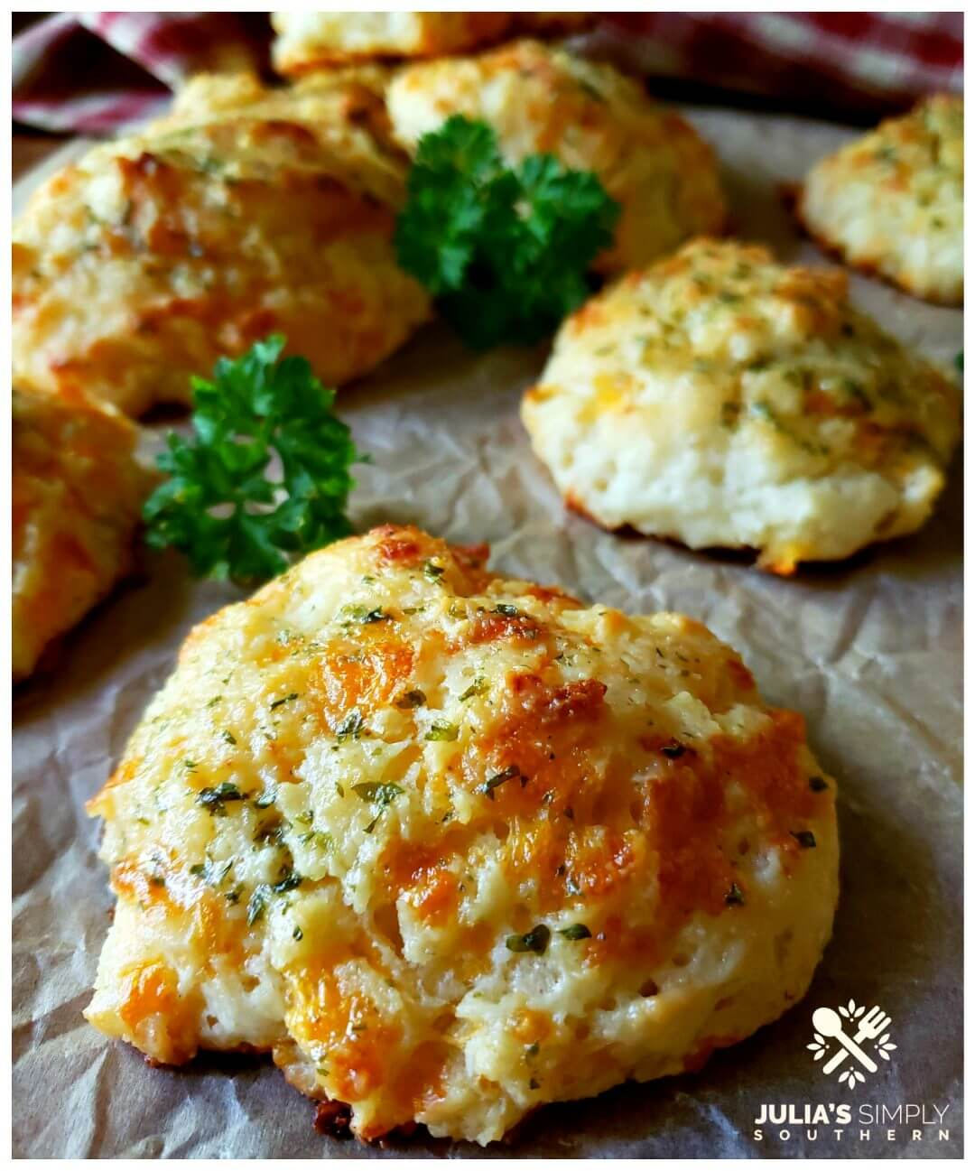 Garlic cheese drop biscuits brushed with an herb butter on a sheet of brown parchment with a few sprigs of parsley