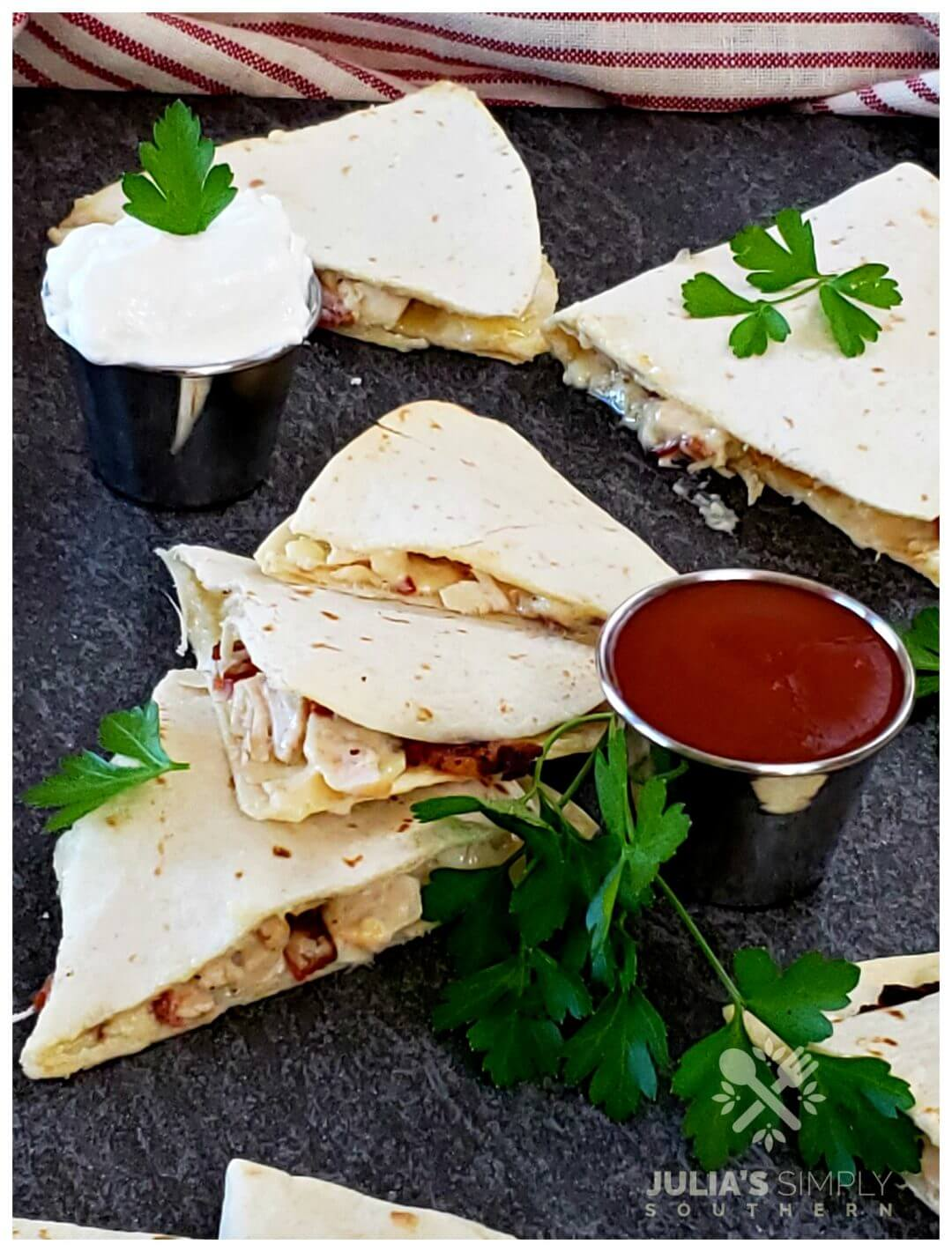 Photo of chicken bacon and ranch quesadillas served with sour cream and hot sauce and garnished with parsley