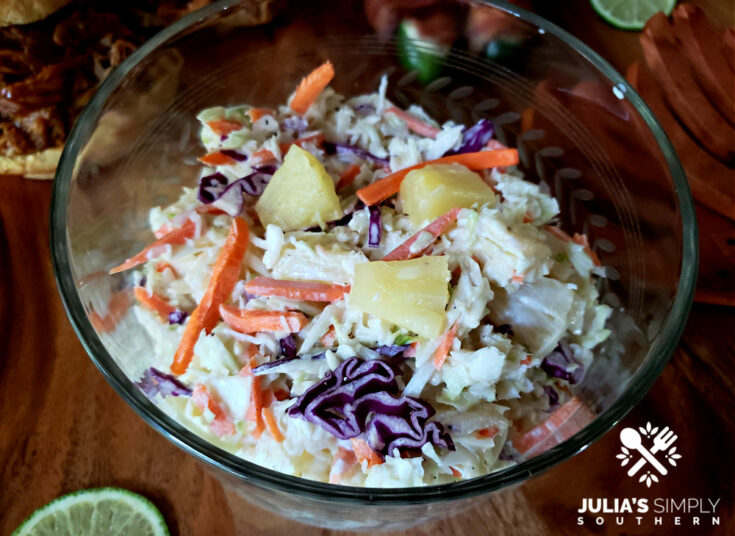 Pineapple coleslaw in a vintage glass bowl with pulled pork sandwiches in the background
