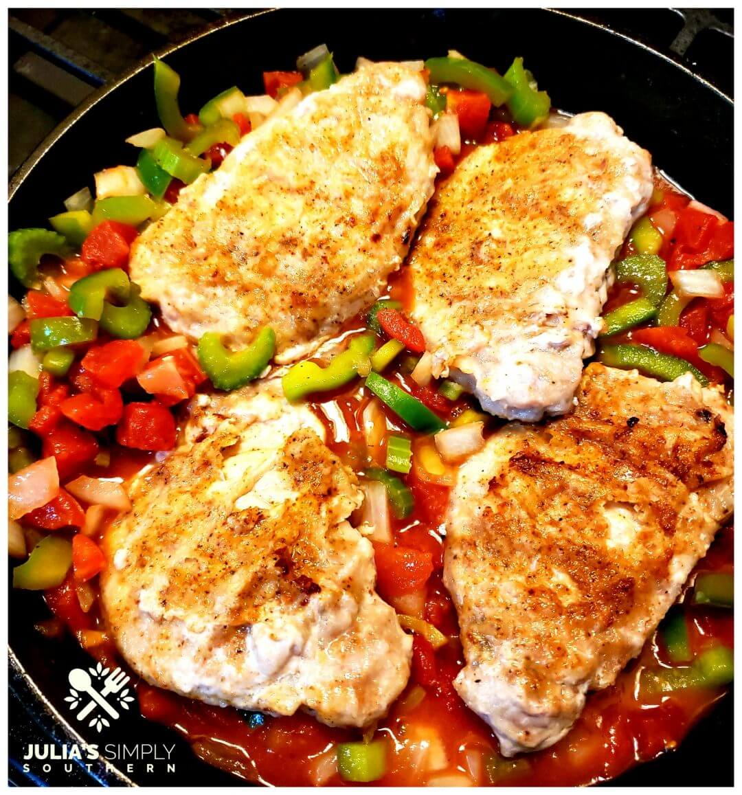 Creole Pork Chops Recipe in a cast iron skillet with the Cajun trinity and tomatoes