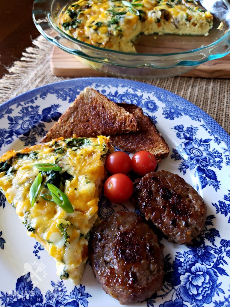 Amazing crustless quiche on a blue and white plate with sausage patties and whole wheat toast