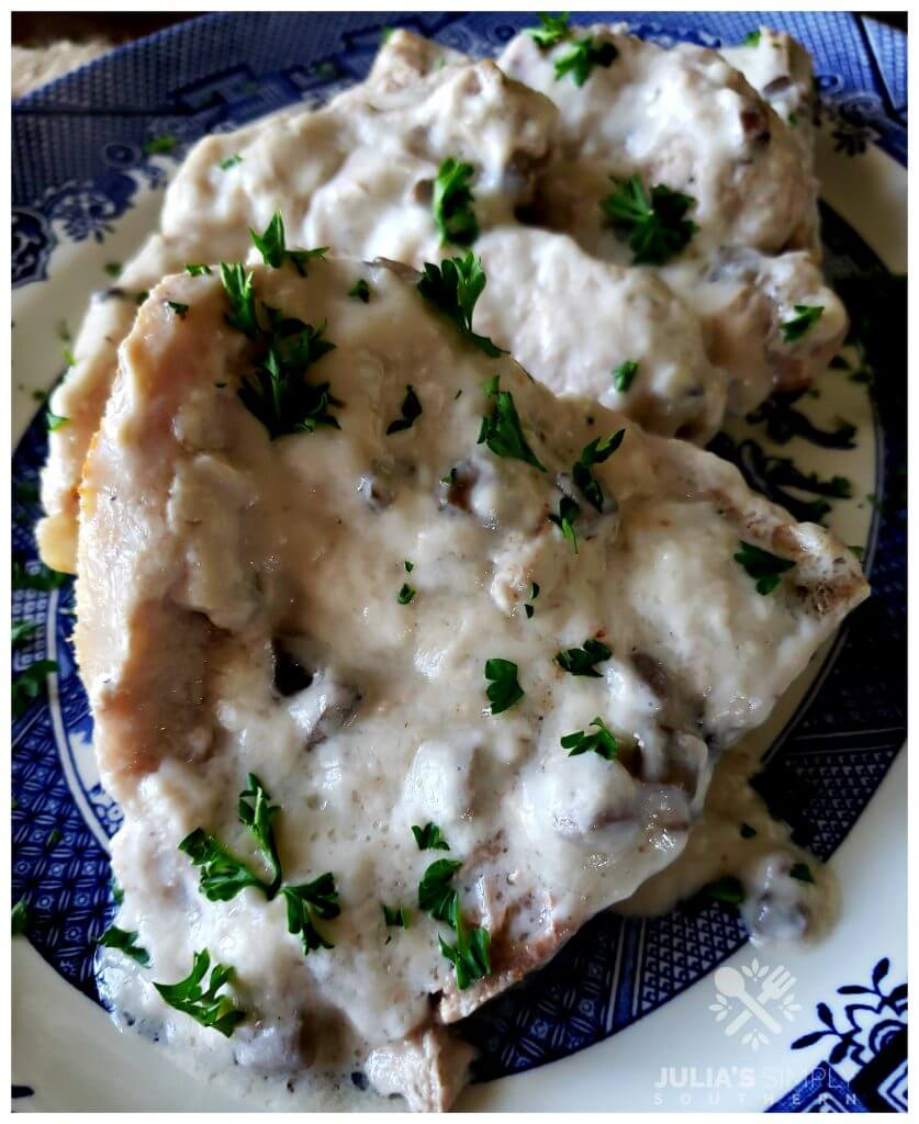 Tender baked pork chops smothered in cream of mushroom soup recipe garnished with parsley