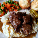 Mississippi Pot Roast served over mashed potatoes with peas, carrots and biscuits