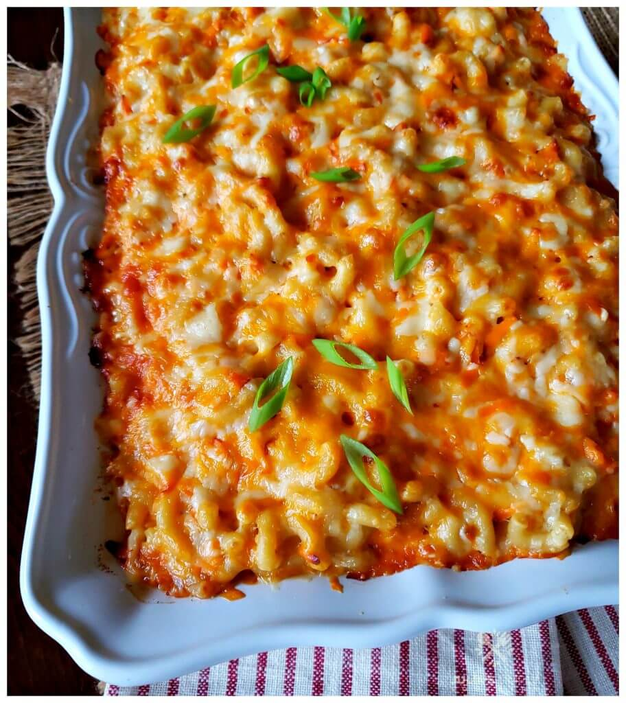 Southern Macaroni & Cheese casserole in a white baking dish garnished with scallions