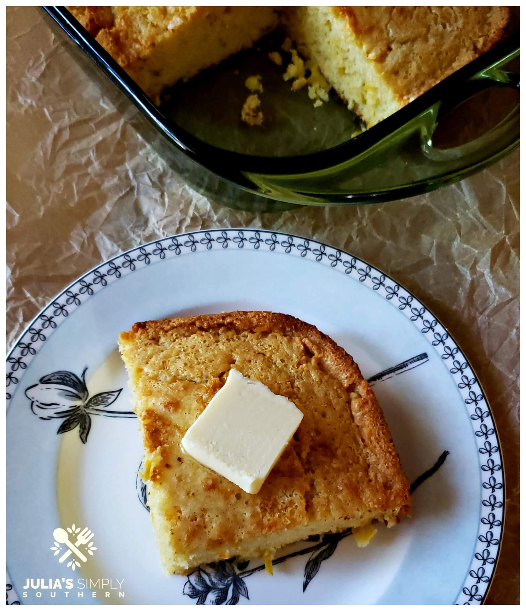 A wedge or rich and moist Southern cornbread on a plate topped with a pat of butter