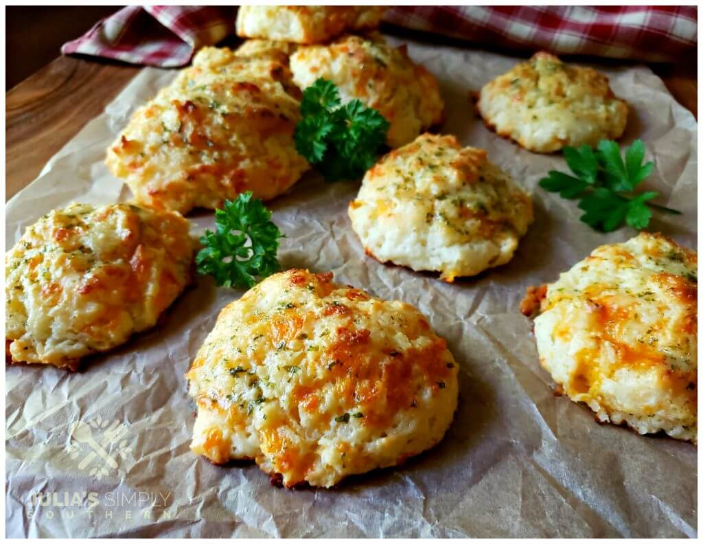 Freshly baked cheese biscuits arranged on a sheet of parchment paper