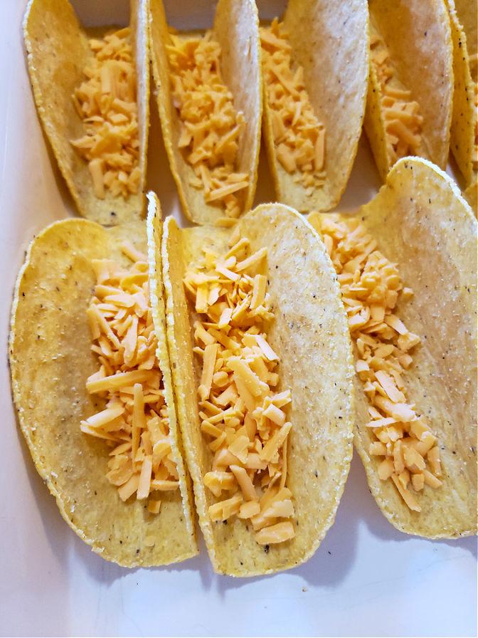 Shredded Cheddar in crunchy taco shells with flat bottoms