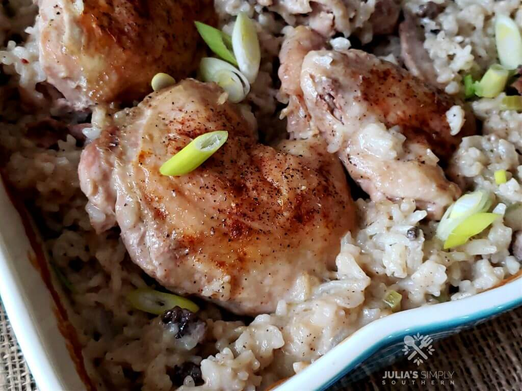 Teal casserole dish with baked chicken and rice garnished with sliced spring onion