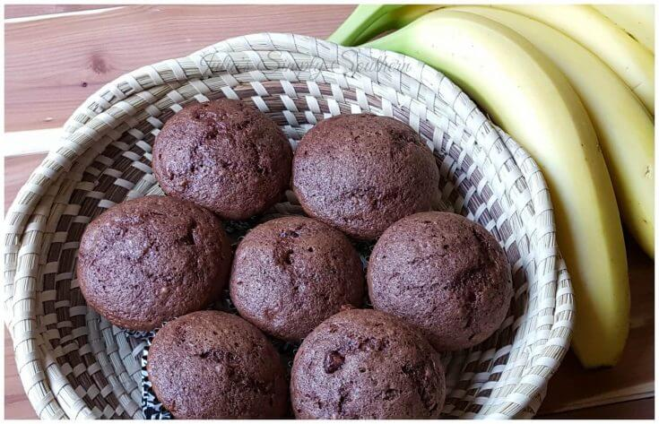 basket with chocolate banana muffins next to a bunch of fresh bananas