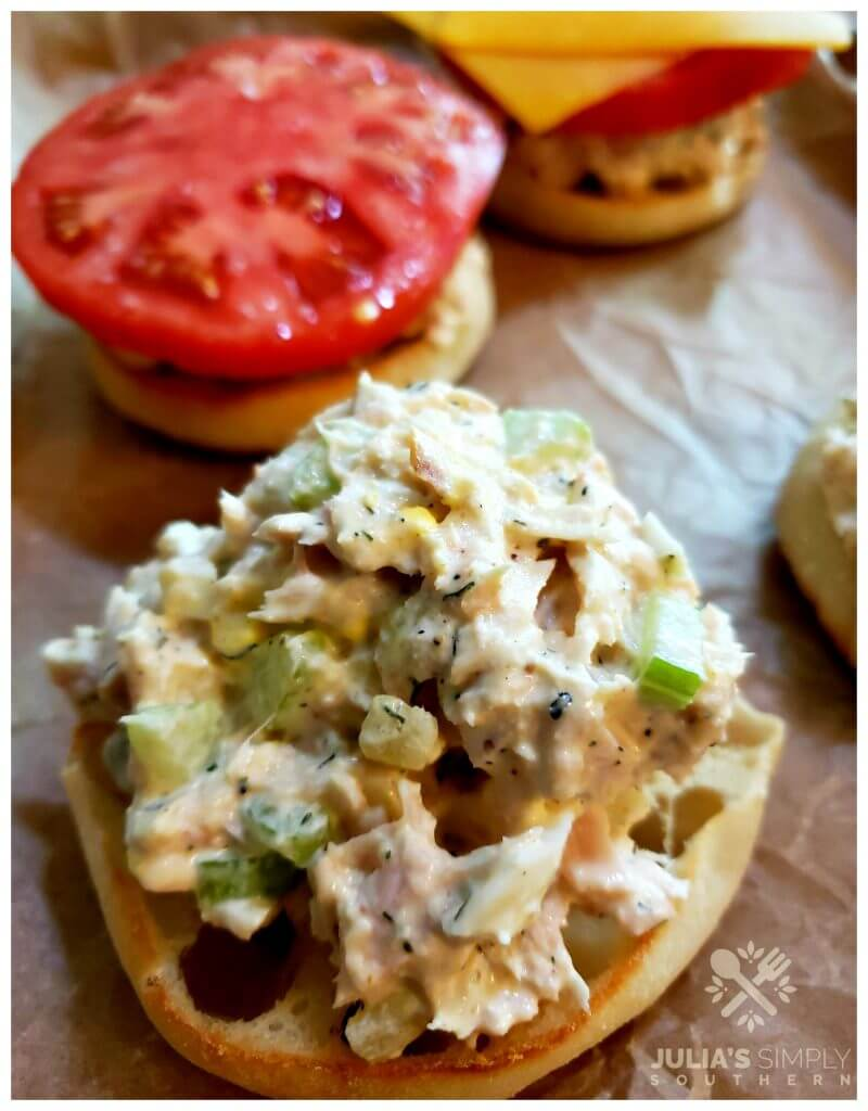 Sheet pan with English muffins topped with tuna salad, tomato and cheese for a tuna melt before toasting in the oven