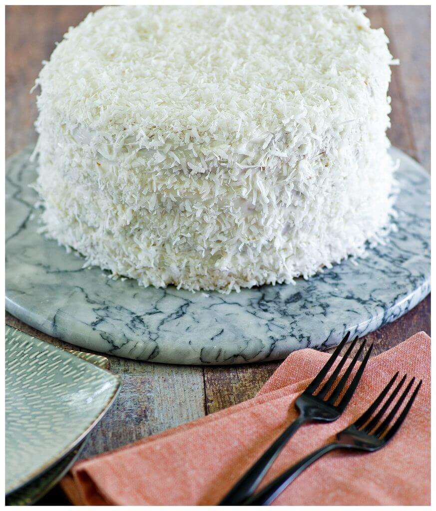 Coconut Cake Frosting with flaked coconut topping on a marble cake plate