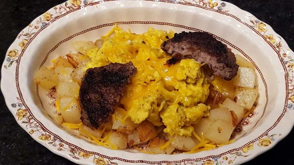 Breakfast bowl meal with potatoes, sausage, eggs and cheese