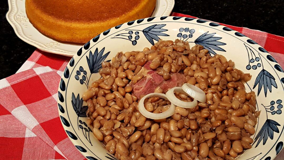 A bowl of pinto beans with a cake of cornbread