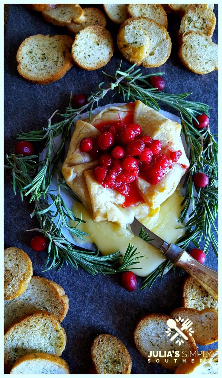 Slate platter with holiday Brie en Croute garnished with cranberry and rosemary served with crustini bread