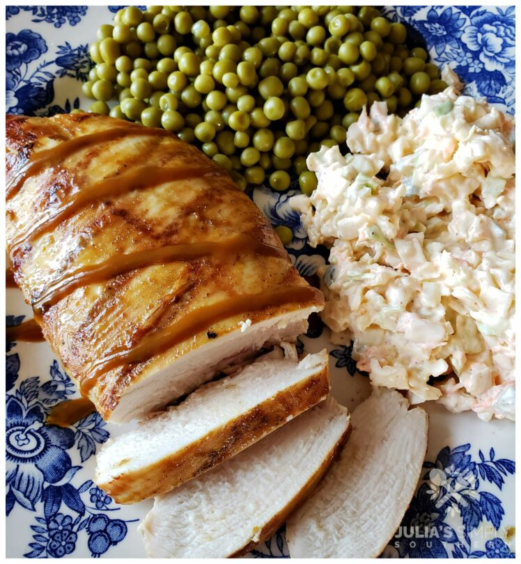 Easy Grilled Carolina Gold Barbecued Chicken Breast on a blue and white plate served with peas and slaw
