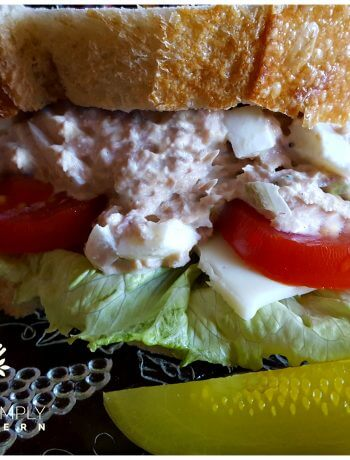 Southern Old Bay Tuna Salad with Duke's Mayonnaise on a glass salad plate with dill pickle spears