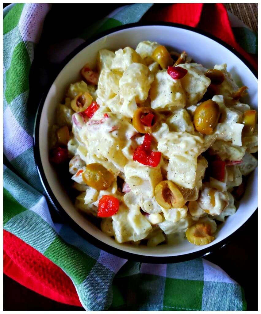A serving bowl filled with potato salad with green olives and pimentos next to colorful napkins