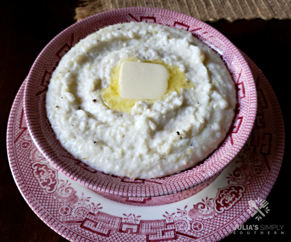 Best Southern style Grits in a red and white bowl with a pat of butter on top