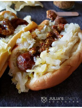 Amazing Beer Braised Bratwurst grilled and on a bun with homemade sauerkraut and course grain mustard